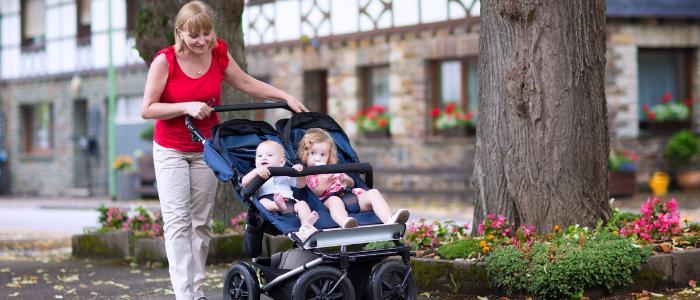 une maman promène ses deux enfants dans une poussette double